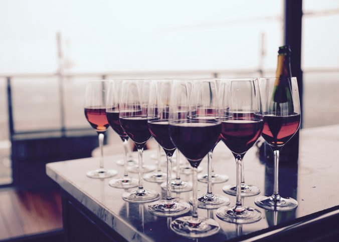 A number of glasses of wine on a bench.